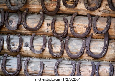 Old rusty horseshoe on a wooden background.
