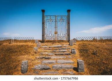Old rusty iron gate in the middle of a field leading to nowhere. Concept of purgatory, limits, frontiers and freedom
