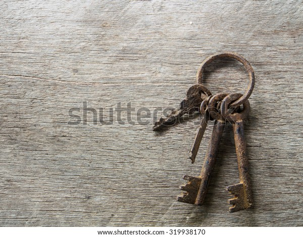 The old rusty key of wooden background