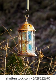 Old rusty lantern hanging above dried branch with blurred background