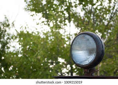 old rusty lantern headlight tractor, agricultural machinery, excavator, combine harvester on the background of green grass trees, glass lens
