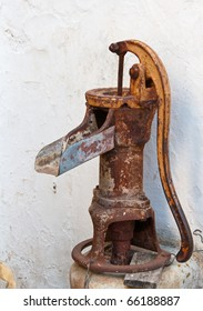 Old and rusty manual water pump in church garden