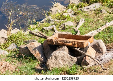 An old rusty metal box placed on stones. A bonfire area covered with an antique drawer