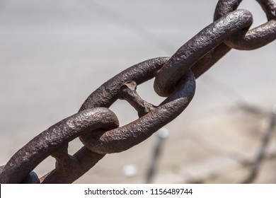 The old rusty metal chain of the anchor of the ship. Giant heavy steel chain leading from land to sea. Yellow mooring line of cargo ship. Ancient rusty Marine anchor chain