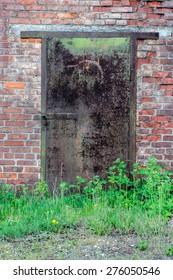 Old rusty metal door with grass