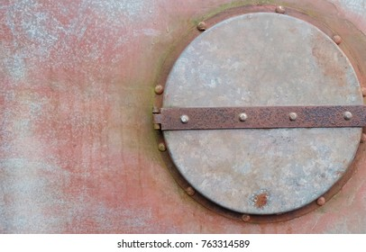 Old rusty metal door with handle and rivets