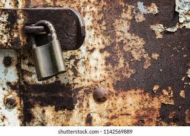 Old and rusty metal door has been locked long time ago