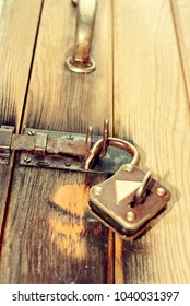 An old rusty metal iron padlock with key on a wood door.