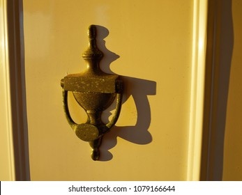 Old and rusty metal knocker on a yellow painted door