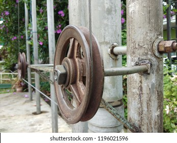 The old and rusty metal pulley and the pulley system is used to draw the flag up and down the flagpole.