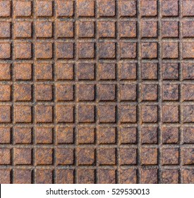 Old rusty metal street sewer drain cover top hatch texture. Close up of steel cover made of squares. Dimension 1x1 cm.