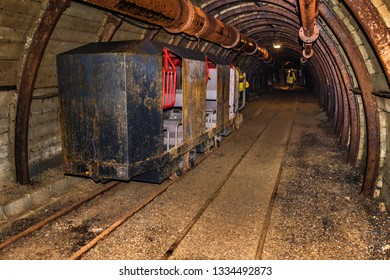 Old and rusty mine train for personnel transfer parked in mine tunnel with wooden timbering