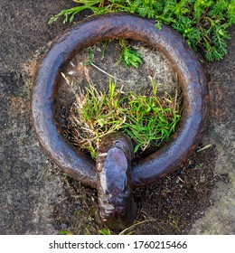 Old rusty mooring ring on canal towpath in shape of letter Q