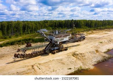 old rusty multi bucket excavator, giant stacker, absetzer in sandy career.