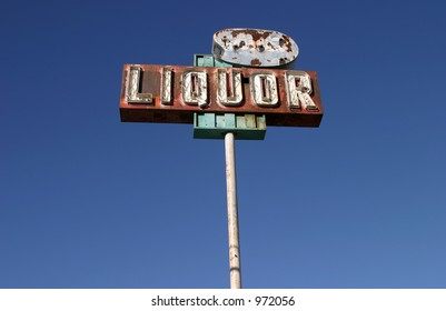 """An Old Rusty Neon """"Liquor"""" sign still stands against a beautiful blue sky in California"""
