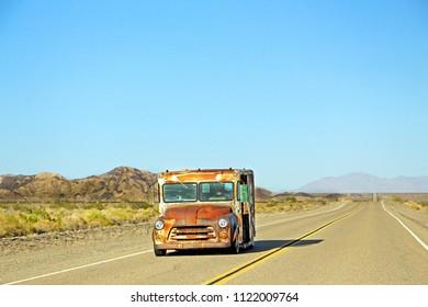Old rusty orange truck / van driving on the empty road / highway in the desert area in California, USA. June 1, 2018.