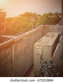 Old and rusty outdoor condenser unit of air conditioner in metal grid container that installed outside high floor of building - Vintage style with selective focus; add flare light.
