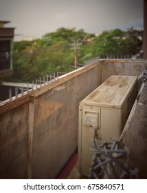 Old and rusty outdoor condenser unit of air conditioner in metal grid container that installed outside high floor of building - Vintage style with selective focus.