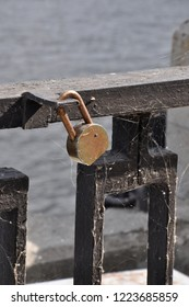 Old rusty padlock hanging on a black bar of an iron parapet covered with cobweb at a river port.