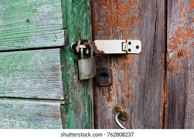 Old rusty padlock on the red and green door