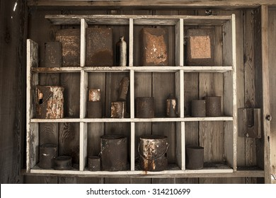 Old, rusty paint cans and solvent containers rest on shelves inside an abandoned wooden shed.