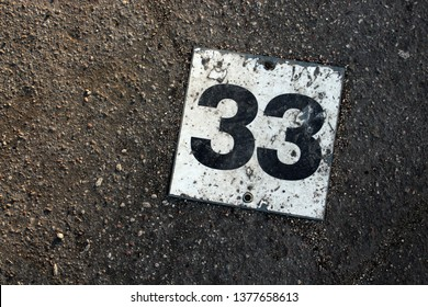 Old rusty parking lot number plate with black and white number 33 on dirty concrete background
