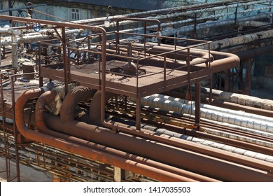 Old rusty pipelines at a chemical plant. Old factory. Industrial photography. Old factory horizontal photography. Metal planks and pipes.