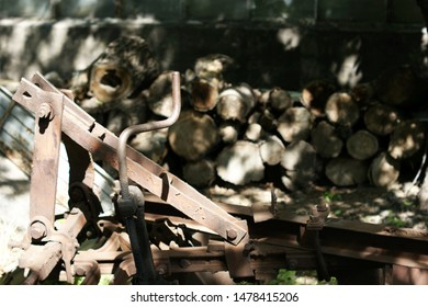 Old rusty plow, details against the background of firewood. An old retro rusted farm machine plow on the ground unused