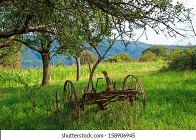Old rusty plow on an orchard
