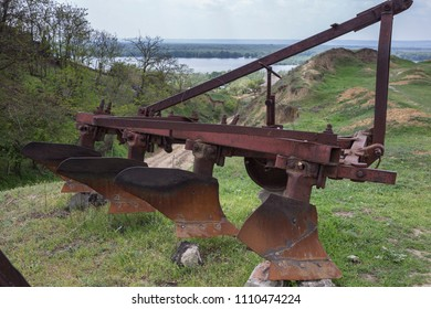 Old rusty plow. This plow is located on top of a hill. Behind the plow is located the canyon and the lake.