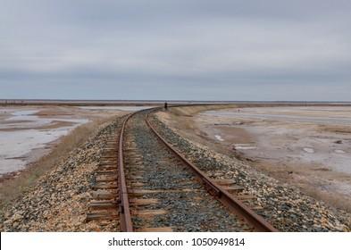 old rusty railroad tracks at salt mining site Lake Baskunchak, Astrakhan region, Russia