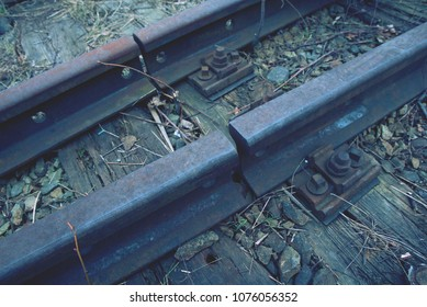Old rusty rails in station aproved for demolition. Railway details, rails joint with gap, nut and screw. Closeup photo with selective focus