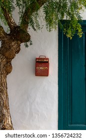 """Old and rusty red mailbox in a white wall between a tree and a door in a traditional Canary house. The word """"mail"""" - in Portugese """"correio"""""""