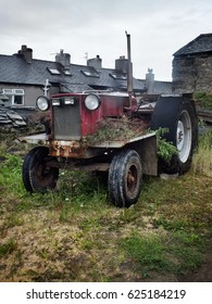 old rusty red tractor in Northumbria with rust and worn tyres in a farmyaerd