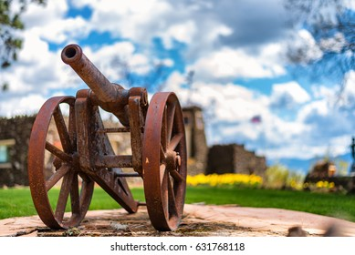 An old rusty relic of a cannon stands guard with tulips and the American flag blowing in the breeze