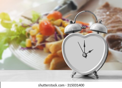 old and rusty retro clock over lunch meal on white dish in restaurant ,abstract background.for time for diet concept.