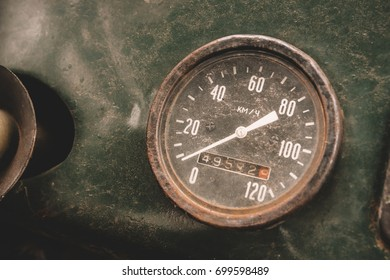 Old rusty round speedometer inside abandoned car.