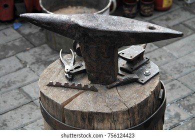 Old rusty rugged anvil on top of other blacksmith tools.