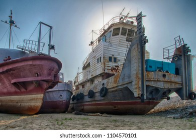 Old rusty and rumpled river tug with some other boats and ships near by. HDR image