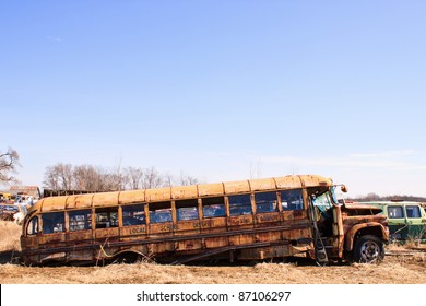 Old rusty school bus partly collapsed in salvage yard