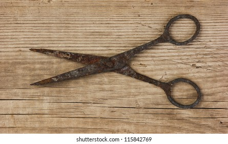 old rusty scissors on the wooden background