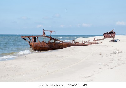 An old rusty ship. The Baltic Sea beach.