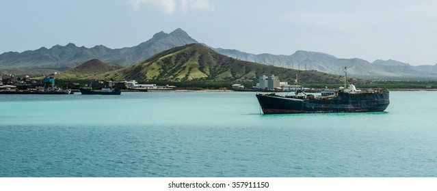 Old rusty Ship in the blue ocean at coast with cloud and green mountain background, Cape Verde island