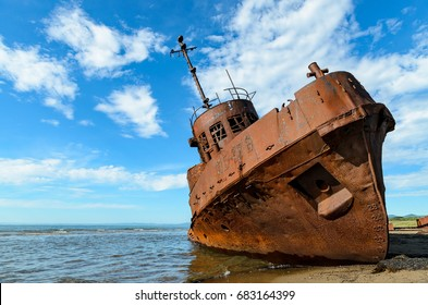 Old rusty ship on the coast on a sunny day.