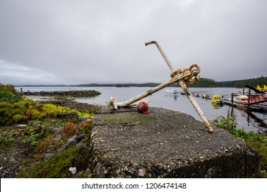 An old rusty ships anchor resting next to the ocean and a marina on a cloudy and gloomy day in Tofino, Vancouver Island, Canada
