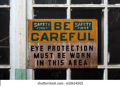 Old rusty sign that says, BE CAREFUL, EYE PROTECTION MUST BE WORN IN THIS AREA.
