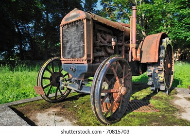Old rusty small tractor in rural grove