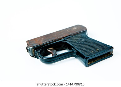 Old rusty starting pistol with black plastic grip, bottom view