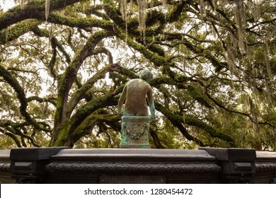 Old rusty statue in a park surrounded by beautiful trees during a foggy morning. Taken in City Park, New Orleans, Louisiana, United States.