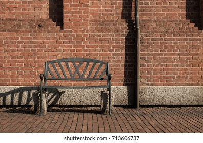Old rusty steel bench on the left side of image with red brick wal and steel pipe